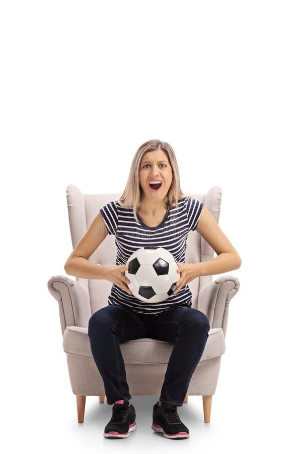 Jovem mulher entusiasmado com um futebol que senta-se em uma poltrona imagens de stock