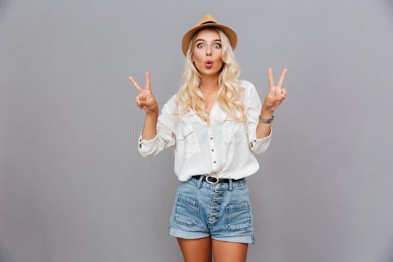 Jovem mulher entusiasmado engraçada que mostra o sinal de paz foto de stock