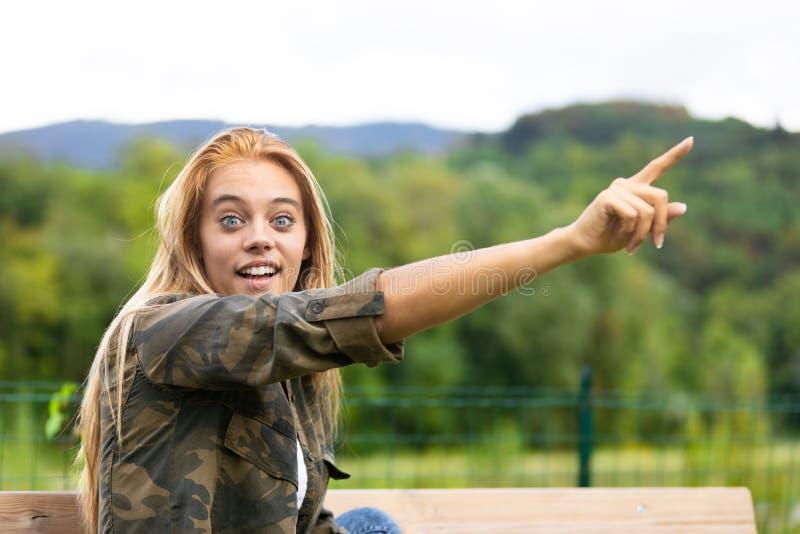 Jovem mulher entusiasmado que aponta acima no ar fotografia de stock royalty free
