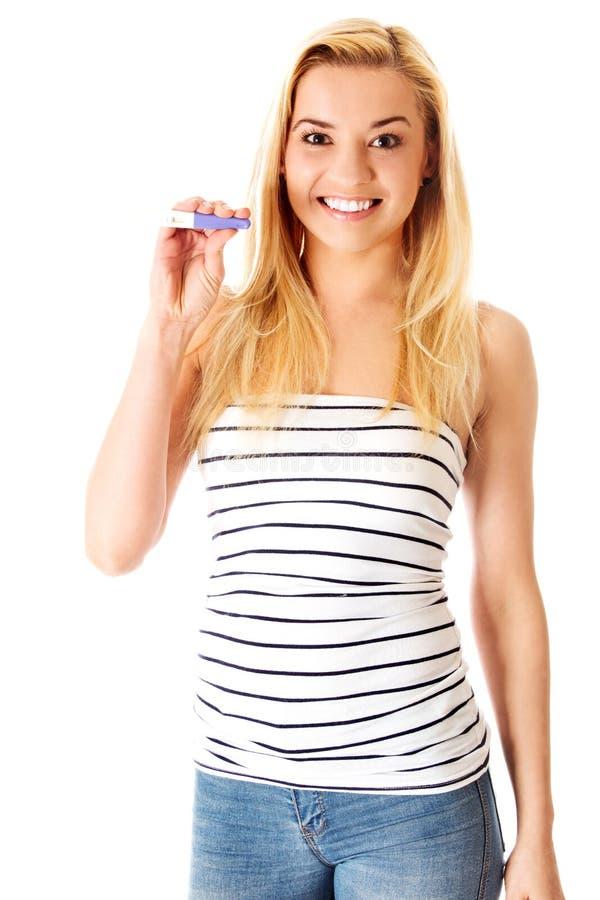 Jovem mulher entusiasmado que mantém o teste de gravidez positivo isolado no branco fotos de stock