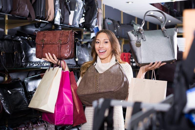 Jovem mulher entusiasmado que seleciona a bolsa nova imagens de stock