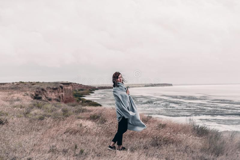 A jovem mulher envolvida na cobertura morna está estando na costa do mar no tempo ventoso imagens de stock royalty free