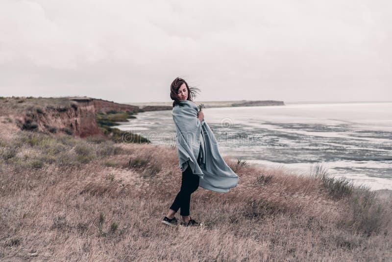 A jovem mulher envolvida na cobertura morna está estando na costa do mar no tempo ventoso imagem de stock