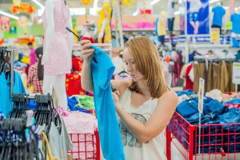 A jovem mulher escolhe a camisa na loja imagem de stock royalty free