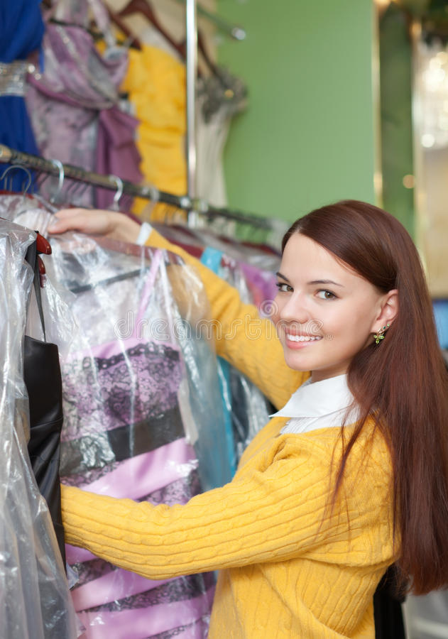 A jovem mulher escolhe o vestido de noite fotos de stock