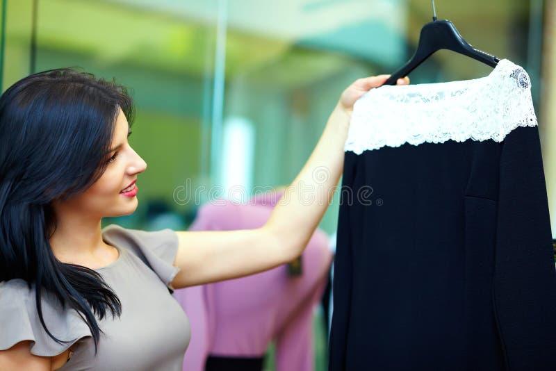 A jovem mulher escolhe o vestido na loja de roupa imagem de stock