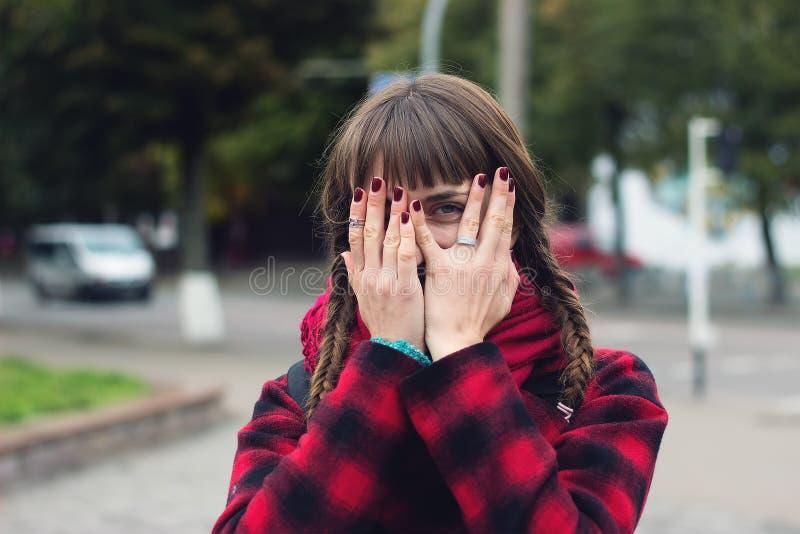 A jovem mulher esconde sua cara em seus palmas e espiões fotografia de stock royalty free