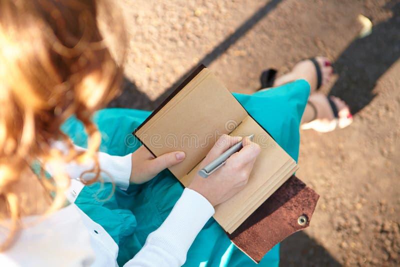 A jovem mulher escreve no caderno. fotografia de stock