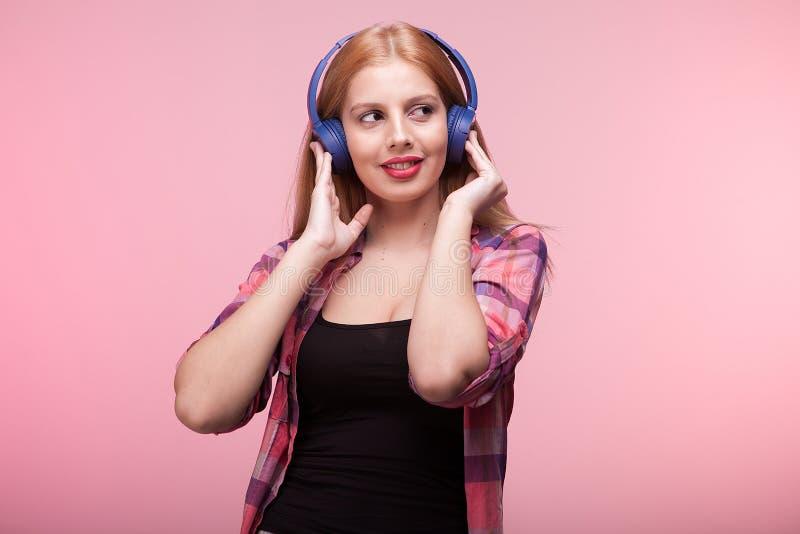 A jovem mulher escuta a música e os olhares afastado fotografia de stock royalty free
