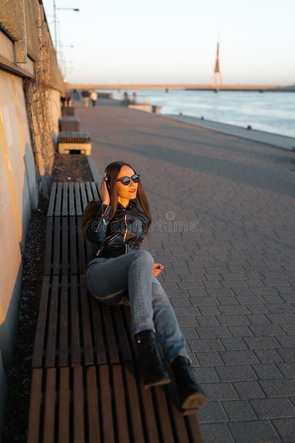 A jovem mulher escuta a música em fones de ouvido fechados através de seu telefone que veste um casaco de cabedal e calças de  fotos de stock