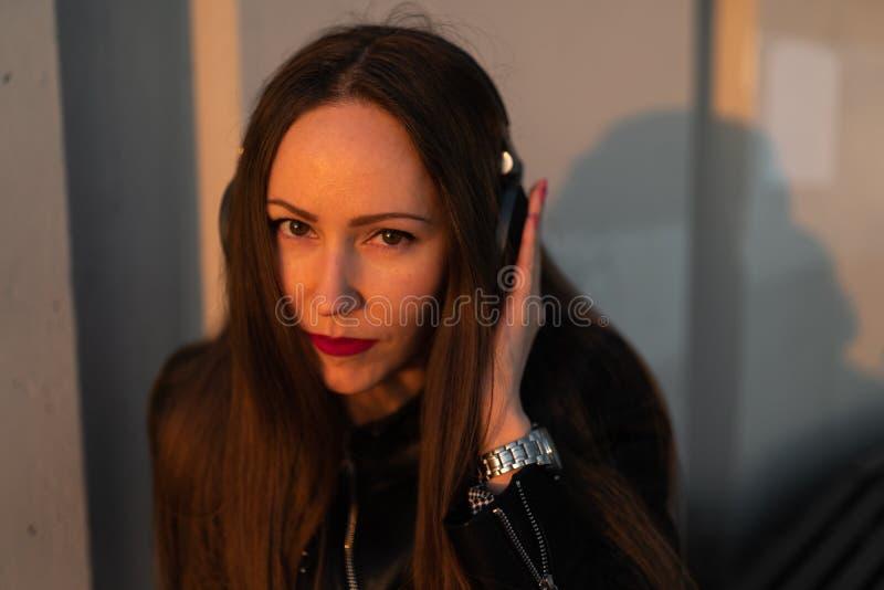 A jovem mulher escuta a música em fones de ouvido fechados através de seu telefone que veste um casaco de cabedal e calças de  imagens de stock royalty free