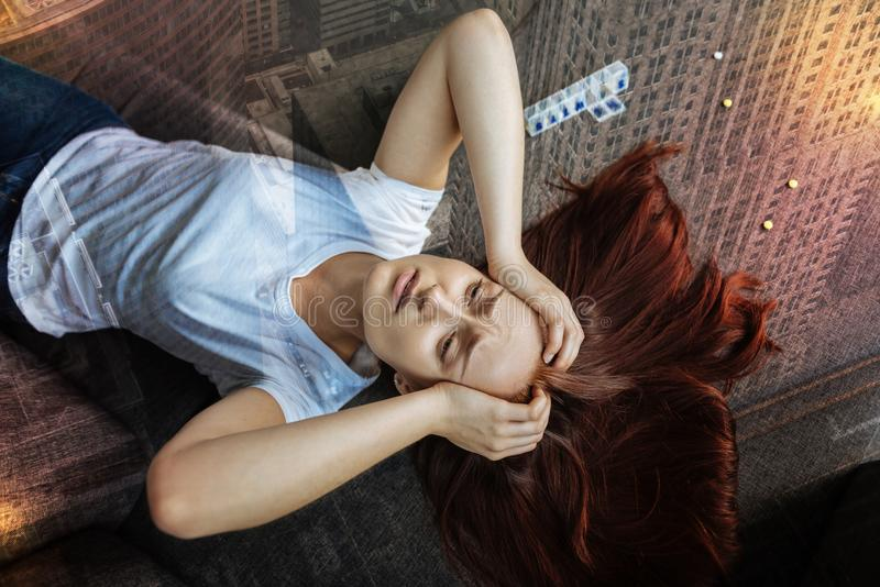 Jovem mulher esgotada que olha de sobrancelhas franzidas e que toca em sua cabeça ao sentir a dor foto de stock