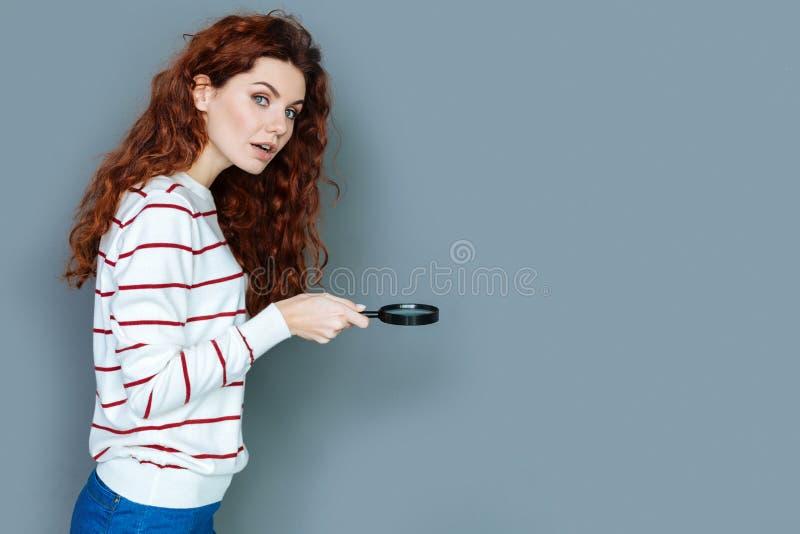 Jovem mulher esperta que usa a lupa fotografia de stock royalty free