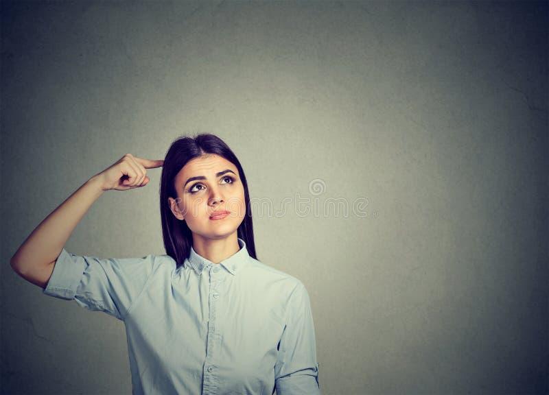 Jovem mulher esquecido que risca a cabeça foto de stock royalty free