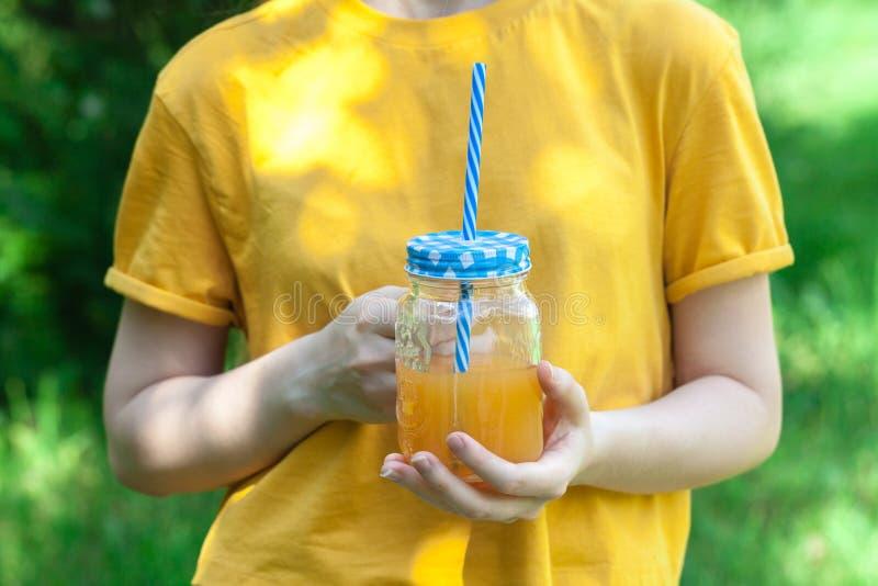A jovem mulher está bebendo o batido saboroso no frasco de vidro com palha bebendo imagens de stock