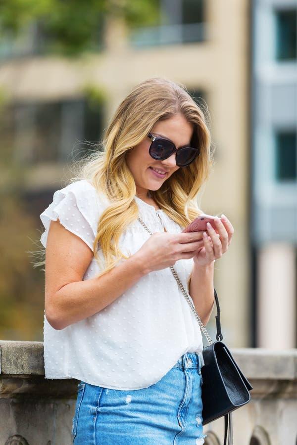 A jovem mulher está com um telefone em uns trilhos da ponte imagens de stock