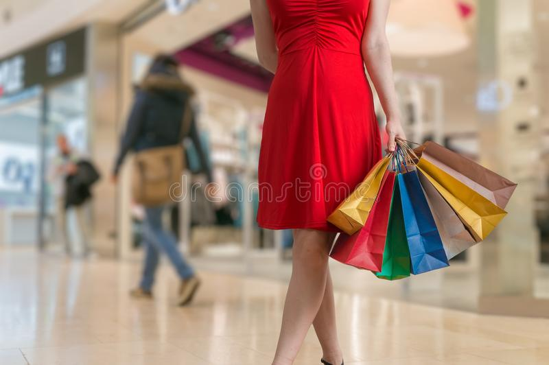 A jovem mulher está comprando na alameda e guarda muitos sacos coloridos imagens de stock