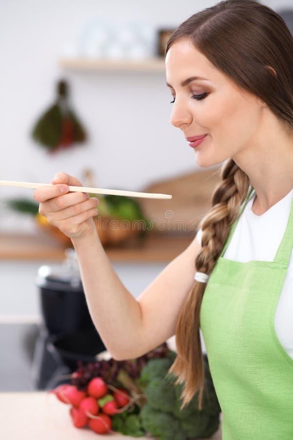 A jovem mulher está cozinhando em uma cozinha A dona de casa está provando a sopa pela colher de madeira imagem de stock royalty free