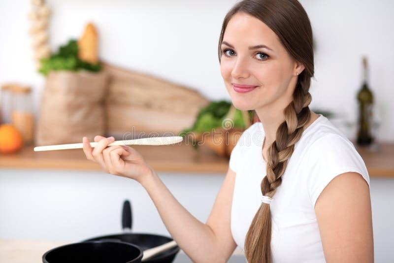 A jovem mulher está cozinhando em uma cozinha A dona de casa está provando a sopa pela colher de madeira fotografia de stock royalty free