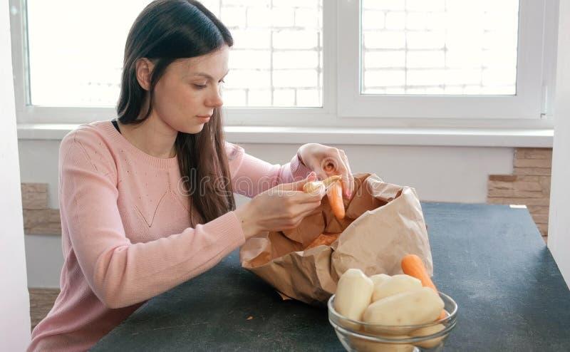 A jovem mulher está descascando a cenoura imagens de stock