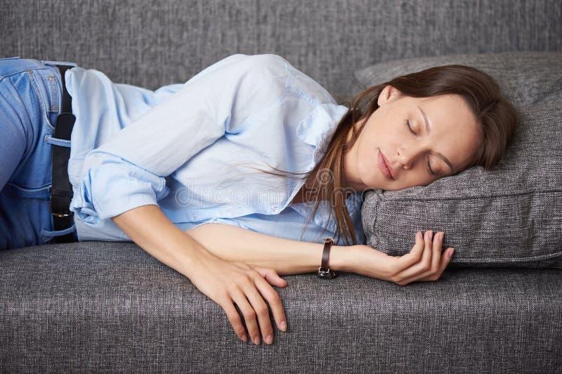 A jovem mulher está dormindo em um sofá fotografia de stock
