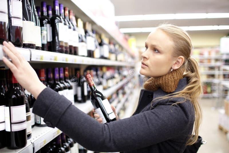A jovem mulher está escolhendo o vinho no supermercado. imagens de stock