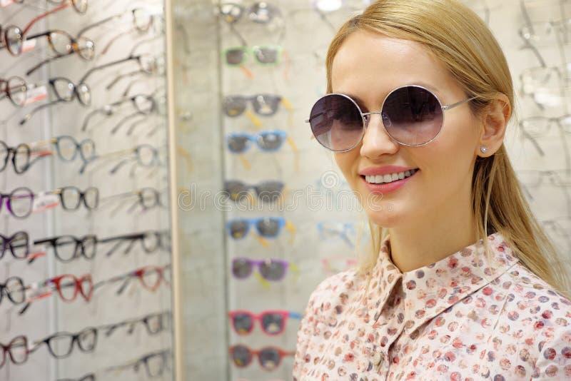 A jovem mulher está escolhendo uns vidros solares na loja do ótico fotografia de stock royalty free