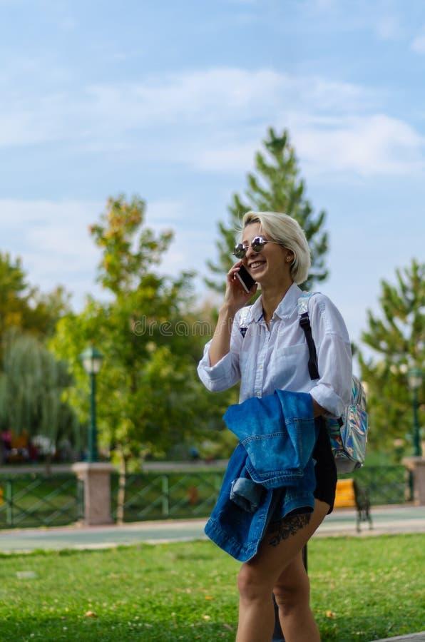 A jovem mulher está falando ao telefone celular e está andando no parque imagens de stock