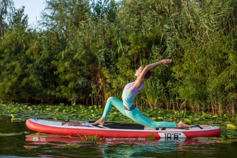 A jovem mulher está fazendo a ioga em um SUP da placa de pá do suporte acima em um lago ou em um rio bonito fotografia de stock