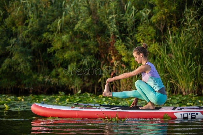 A jovem mulher está fazendo a ioga em um SUP da placa de pá do suporte acima em um lago ou em um rio bonito foto de stock