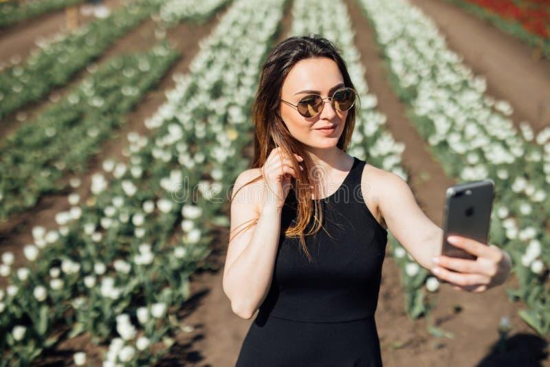 A jovem mulher está fazendo um selfie em um campo de flor colorido das tulipas foto de stock