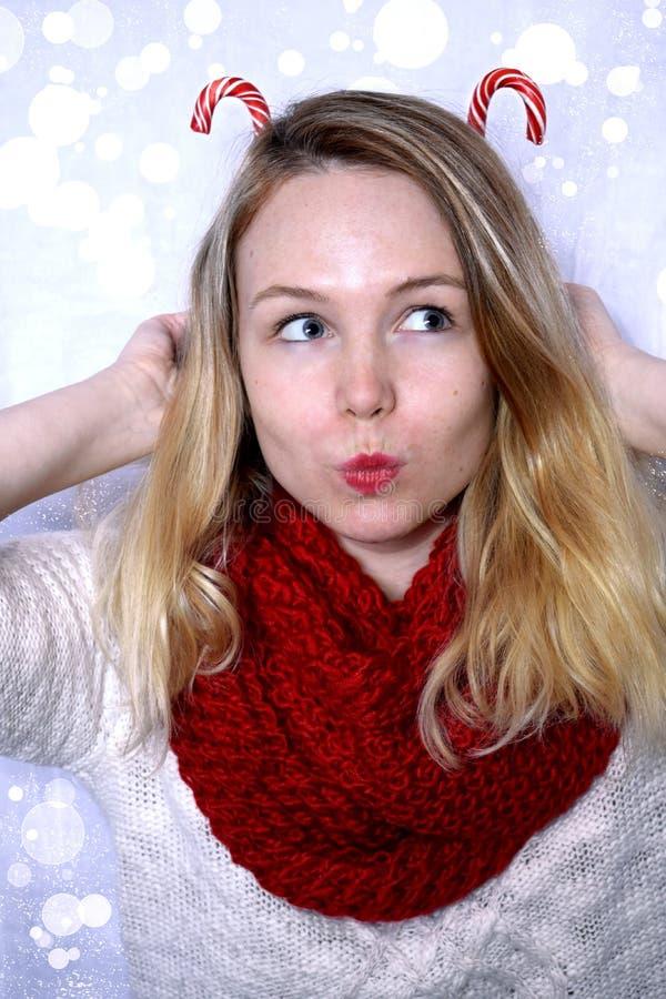 A jovem mulher está guardando bastões de doces atrás de sua cabeça que forma chifres engraçados foto de stock