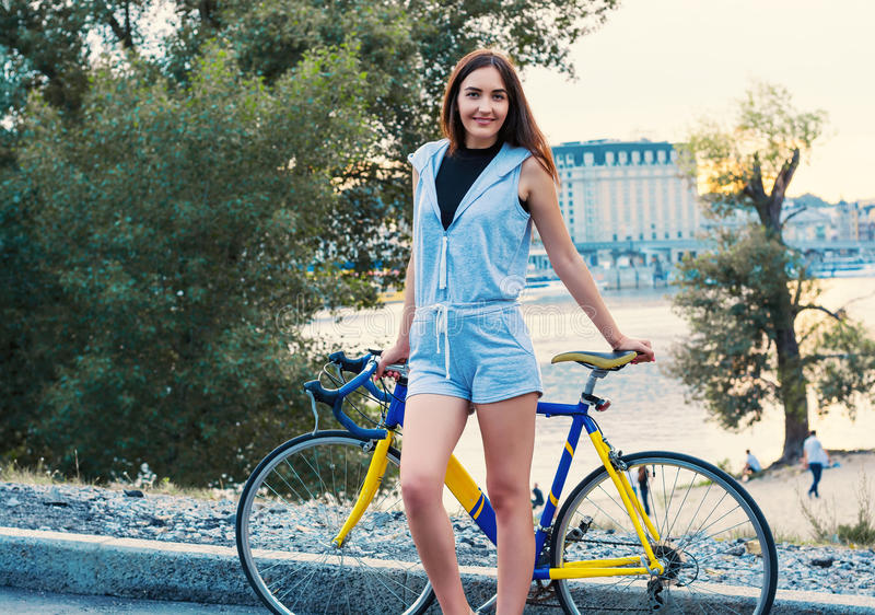 A jovem mulher está-me com uma bicicleta na ponte sobre o rio fotografia de stock royalty free