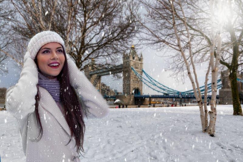 A jovem mulher está na frente da ponte da torre em Londres e aprecia a neve imagens de stock