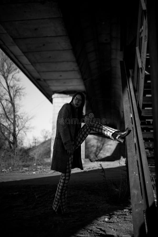A jovem mulher está na máscara sob a ponte Imagem preto e branco imagens de stock royalty free
