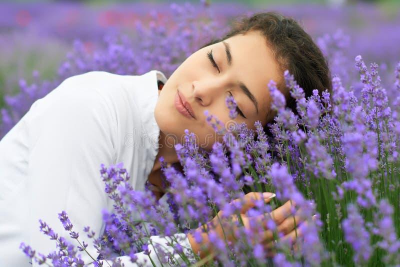 A jovem mulher está no campo da alfazema, retrato bonito, close up da cara, paisagem do verão com as flores vermelhas da papoila fotos de stock royalty free