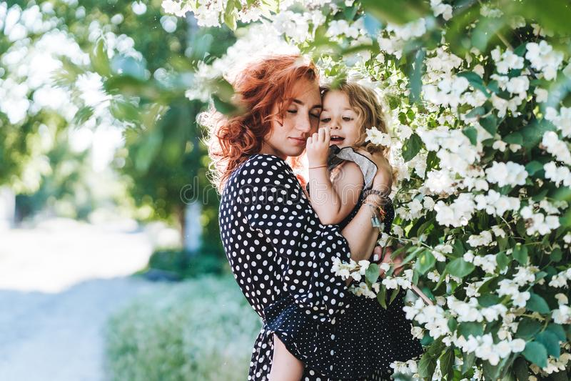 A jovem mulher está o jasmim próximo com uma filha pequena fotografia de stock
