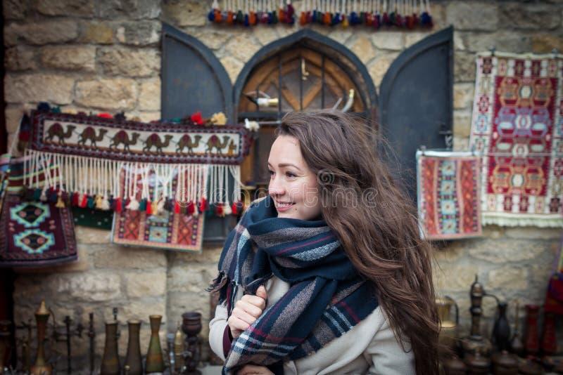 A jovem mulher está perto de uma mostra bonita no mercado oriental fotos de stock royalty free