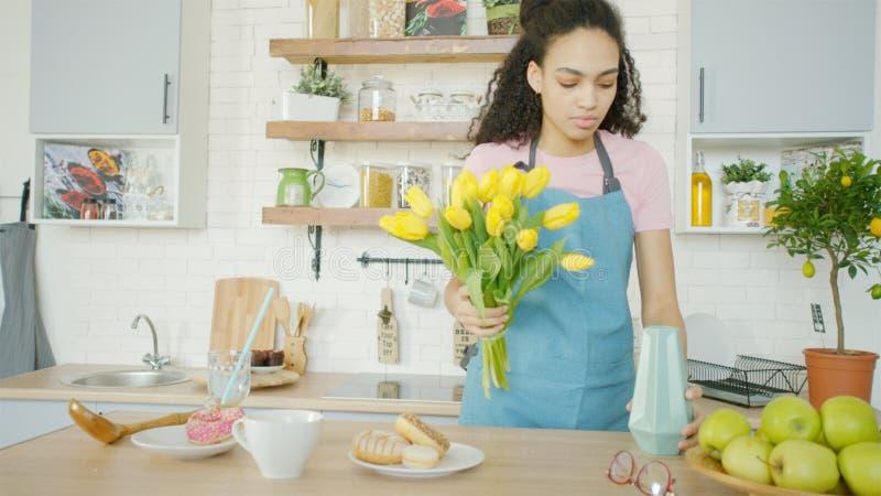 A jovem mulher está pondo flores em um vaso sobre a mesa de jantar fotos de stock