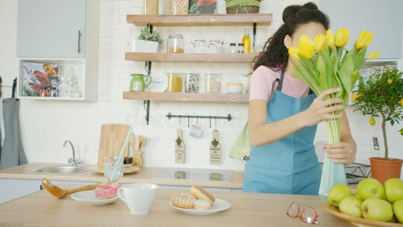 A jovem mulher está pondo flores em um vaso sobre a mesa de jantar fotos de stock royalty free