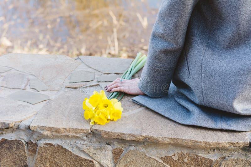A jovem mulher está sentando-se na beira com as flores amarelas brilhantes fotografia de stock royalty free