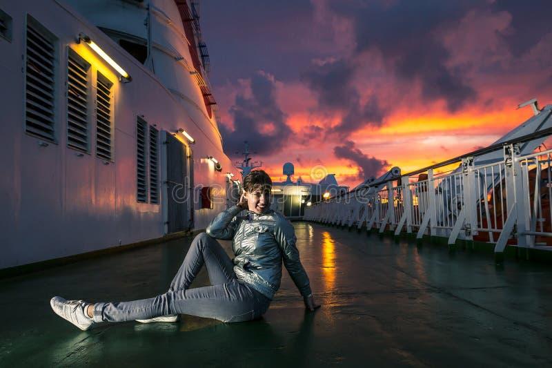A jovem mulher está sentando-se na plataforma durante o por do sol fotografia de stock