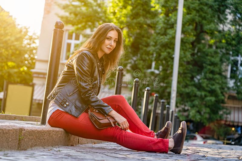 A jovem mulher está sentando-se no pavimento em calças vermelhas, revestimento preto fora Fotografia da forma da rua com menina ' foto de stock