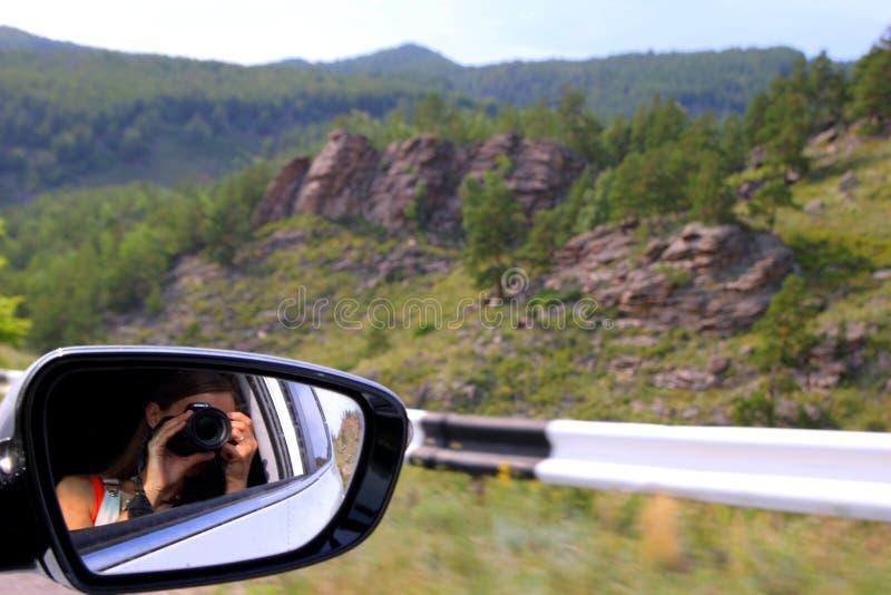 A jovem mulher está tomando uma foto para o Mountain View de um carro imagens de stock royalty free