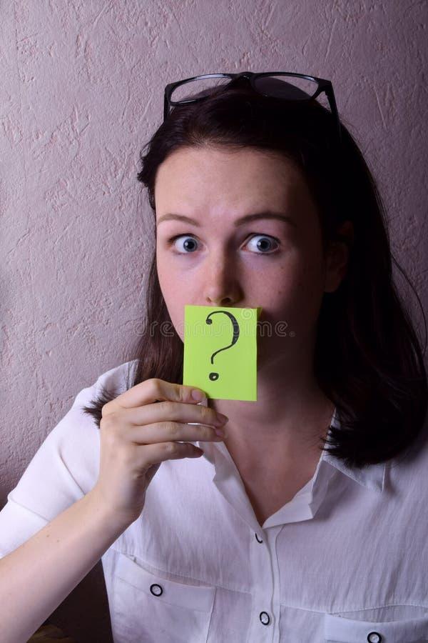 A jovem mulher est? guardando uma etiqueta verde com um ponto de interroga??o imagem de stock