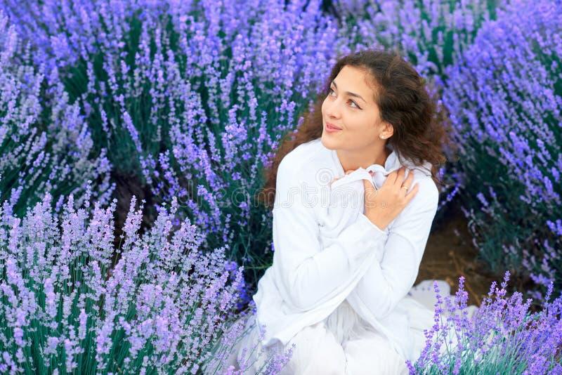 A jovem mulher est? no campo de flor da alfazema, paisagem bonita do ver?o fotos de stock royalty free