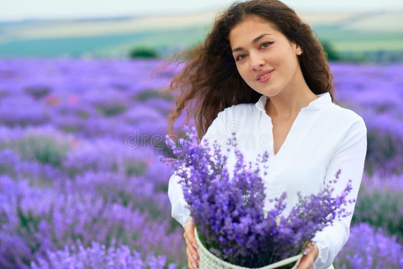 A jovem mulher est? no campo de flor da alfazema, paisagem bonita do ver?o imagem de stock royalty free