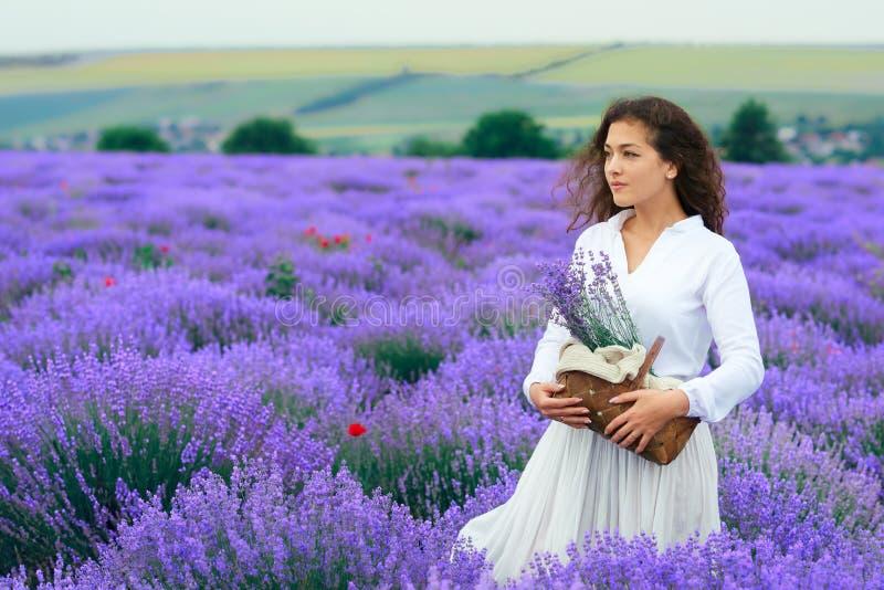 A jovem mulher est? no campo de flor da alfazema, paisagem bonita do ver?o fotografia de stock