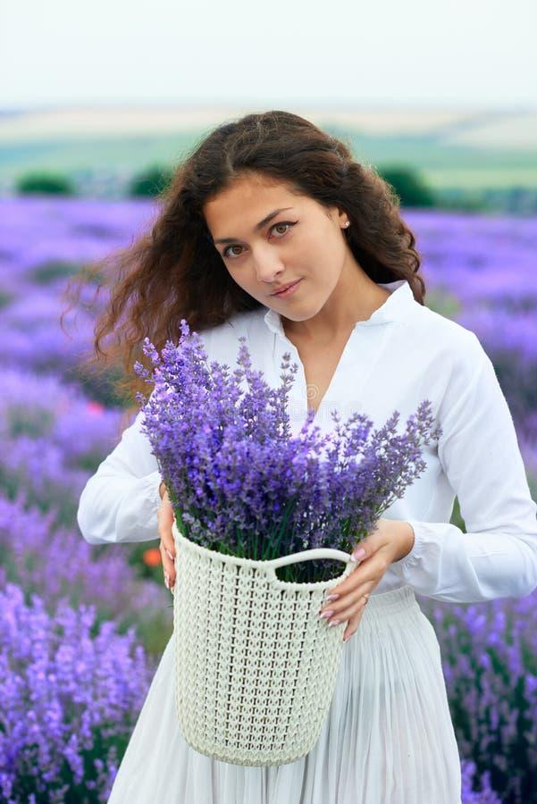 A jovem mulher est? no campo de flor da alfazema, paisagem bonita do ver?o imagem de stock