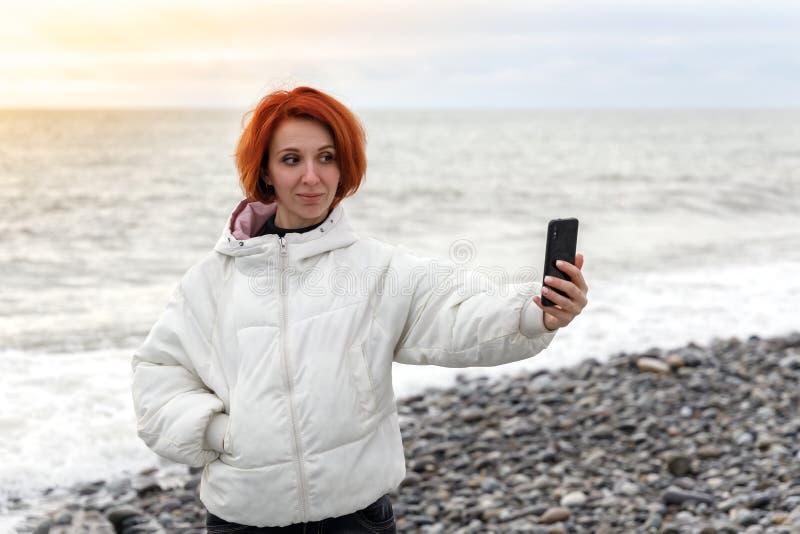 A jovem mulher est? no litoral do seixo contra o por do sol e toma um selfie imagens de stock royalty free